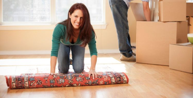 young woman kneeling on floor, starting to roll out an area rug