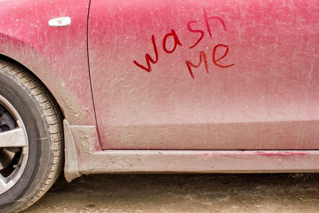 door of a dirty red auto with WASH ME written in the dirt